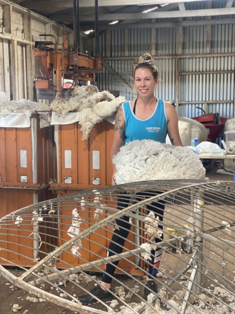 Woman standing with clump of wool in a shed.