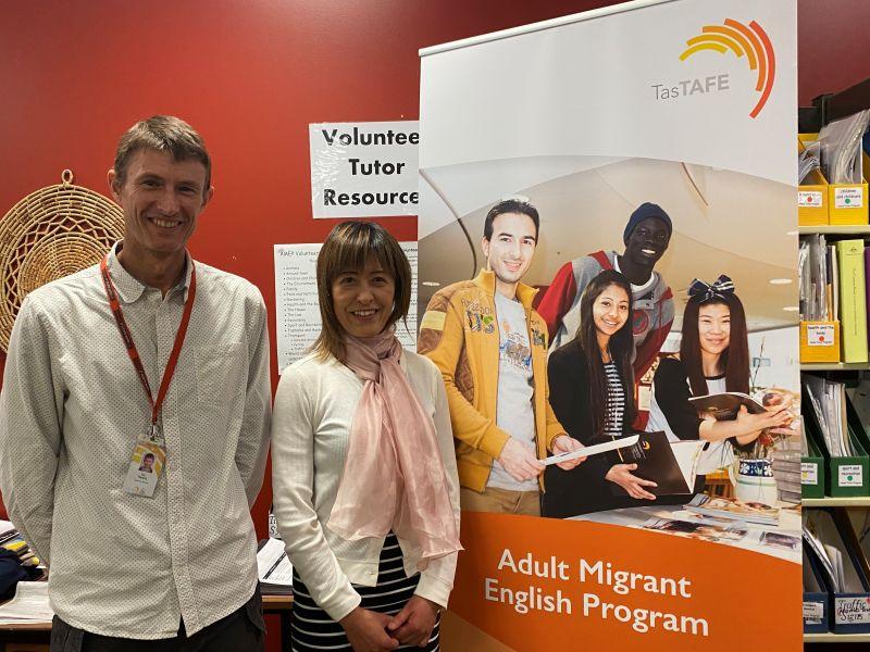 Ian and Hiroko posing in front of migrant program banner