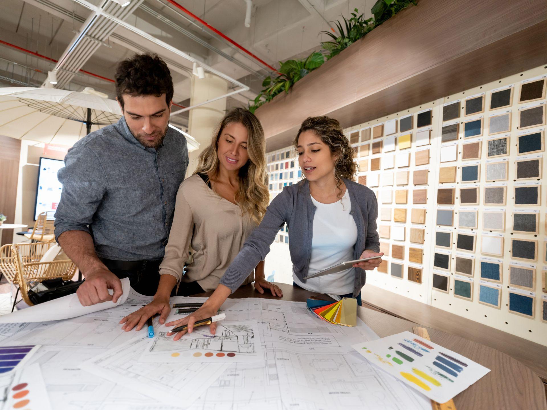 Three people working on an interior design plan